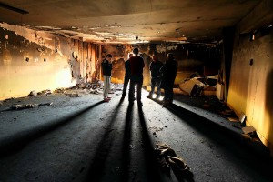 St Saviour's GAA Club members pictured inside their burned-out clubhouse on Saturday morning after an overnight fire at both the club and the local Youth Resource Centre (inset) left the community in a state of shock.  Photos: Noel Ryan
