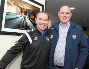 Tony Corcoran (St Saviour's GAA Club) pictured with Waterford Senior Football manager, Tom McGlinchey, at the official re-opening of the Saviour's Clubhouse; with a photo of the clubhouse's fire damaged interior (also photographed by Noel Browne) hanging behind them.