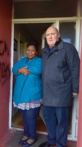 Cllr John Hearne pictured with Meriam Ajayi and (inset) some of the graffiti sprayed on the house.