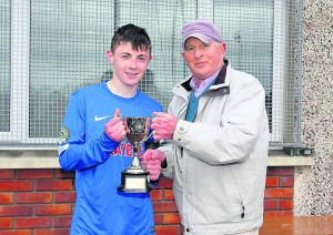 Mount Sion captain Justin Croke receives the Munster U-17 SFAI Schools Cup from Matt Keane.