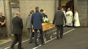 The remains of the late Austin Deasy are received at Saint Mary's Church in Dungarvan.  | Still: RTE