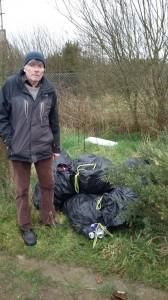 Paddy Houlihan alongside sacks which were dumped in the area last week.