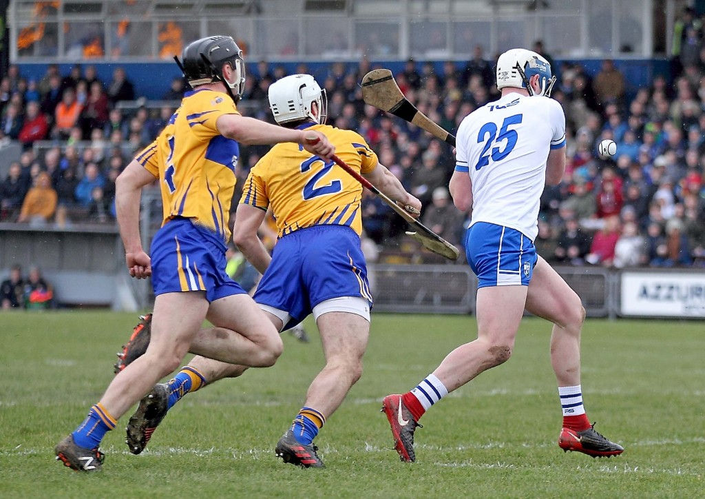 Waterford's Stephen Bennett is about to be hooked as he shoots at goal but the subsequent loose ball was pounced on by Patrick Curran who whipped the ball to the Clare net for his side's only goal at Walsh Park on Sunday last.| Photos: Noel Browne
