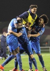 Waterford FC players mob Courtney Duffus following his 80th minute winner against champions Cork City at the RSC on Friday last.  Inset: Gavin Holohan celebrating victory following a tempestuous finish. | Photos: Noel Browne