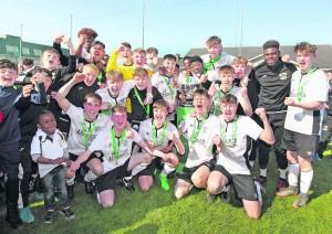 Tramore players and mentors celebrate their victory over St. Kevin's Boys in the FAI Junior Cup