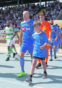 Waterford captain Paul Keegan leads his team out with mascot Lucas O'Neill on Sunday last at the RSC