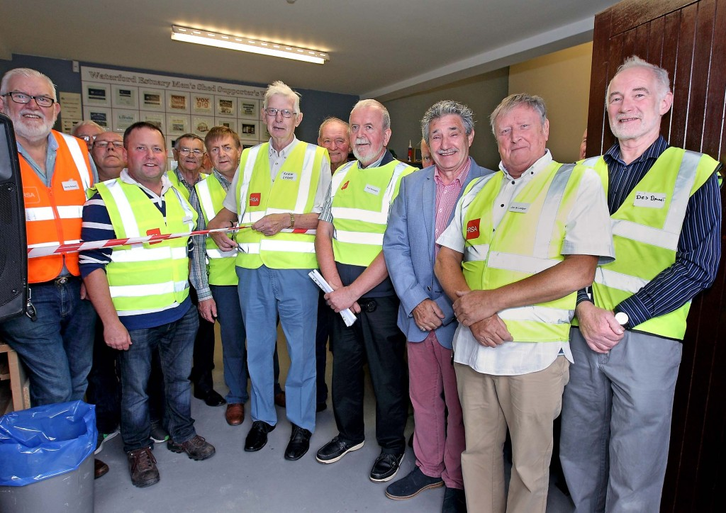Waterford Estuary Men's Shed chairman, John Lyons in the presence of fellow Men's Shed members about to cut the ribbon to officially open the newly renovated Men's Shed building in Passage with Minister for Training, Skills and Innovation, John Halligan TD also included.