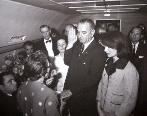 Lyndon B Johnson is sworn in as President of the United States by Federal Judge Sarah Hughes aboard Air Force One. Johnson is flanked by Jacqueline Kennedy (right) and his wife, Lady Bird Johnson (left). Judge Hughes can be seen in the lower-left corner with her back to the camera.