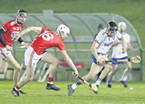 Waterford's Mikey Kearney flicks the ball away from Cork's David Griffin.