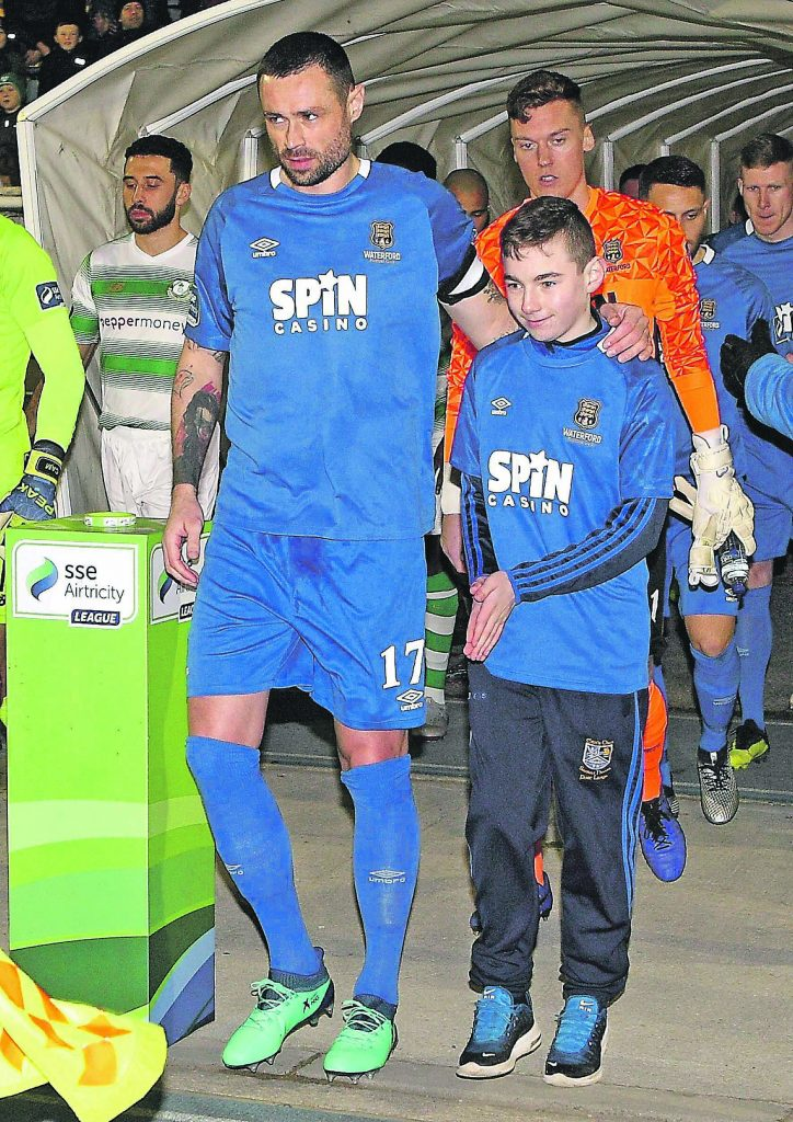 Waterford FC captain, Damien Delaney pictured with the TEVA sponsored mascot, Ben Leahy as they head out on the RSC pitch for the club's first premier league game of the year.