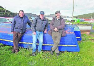 "Thomas Connors, Philip Gunnip and Tommy ""Tucker"" Burke next to the fishing boats lying idle in Passage East. Photos: Noel Browne."