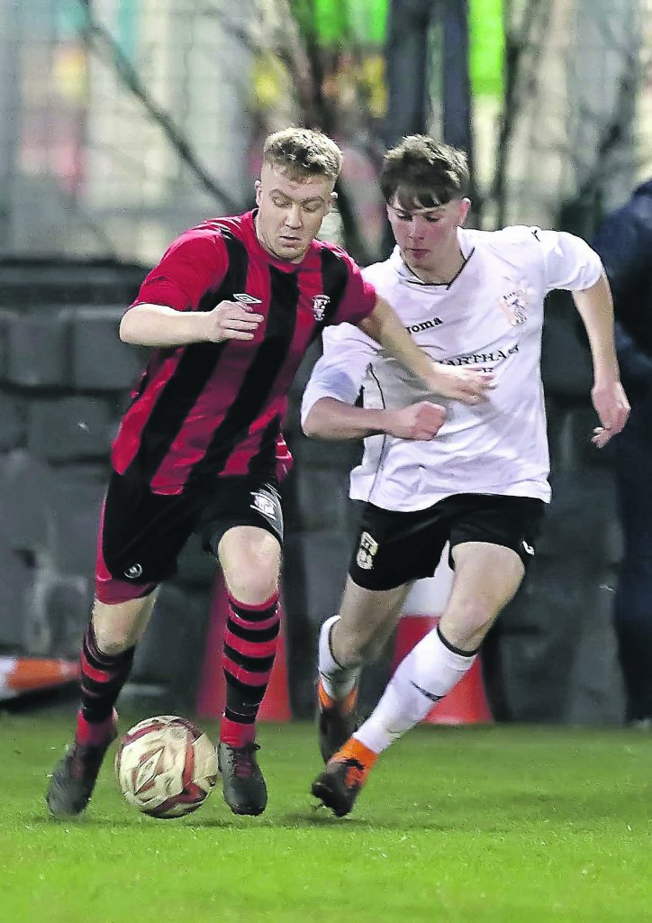 Bohs Dylan Brophy holds off the challenge from Tramore's Cameron Kent