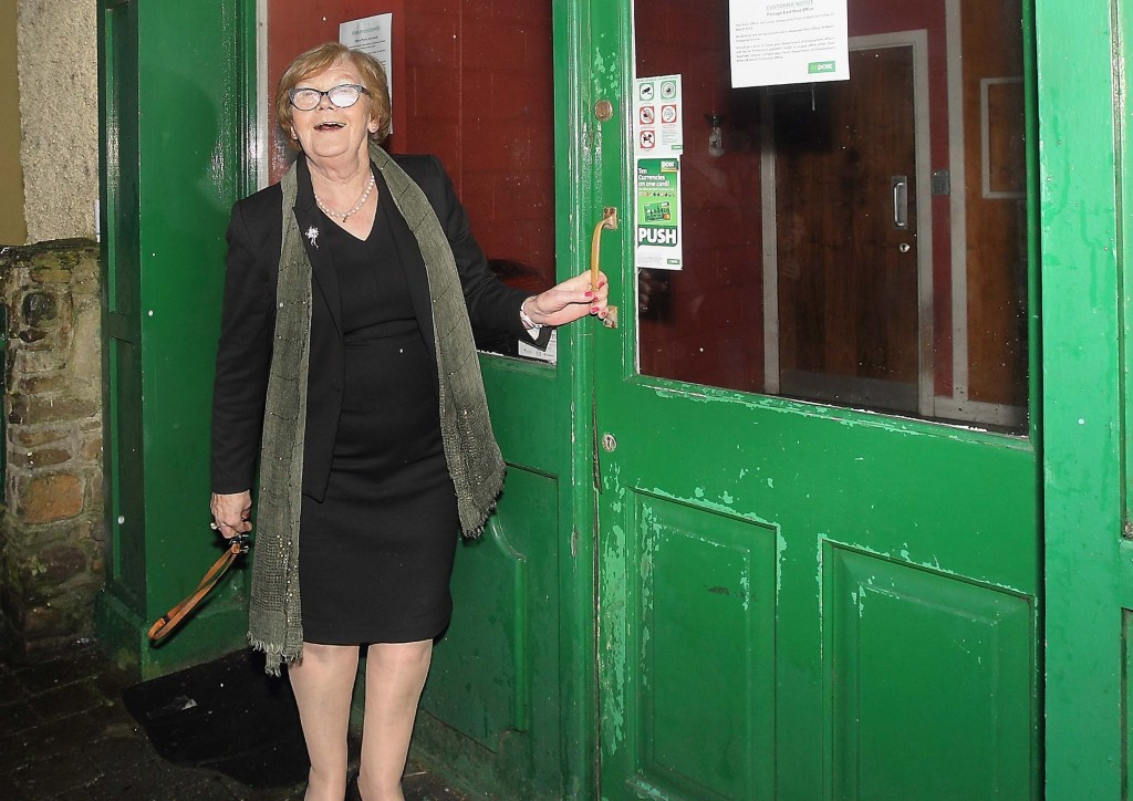 Ann Carey locks the door of the Passage East Post Office for the final time following its closure on Friday last. Photos: Noel Browne.