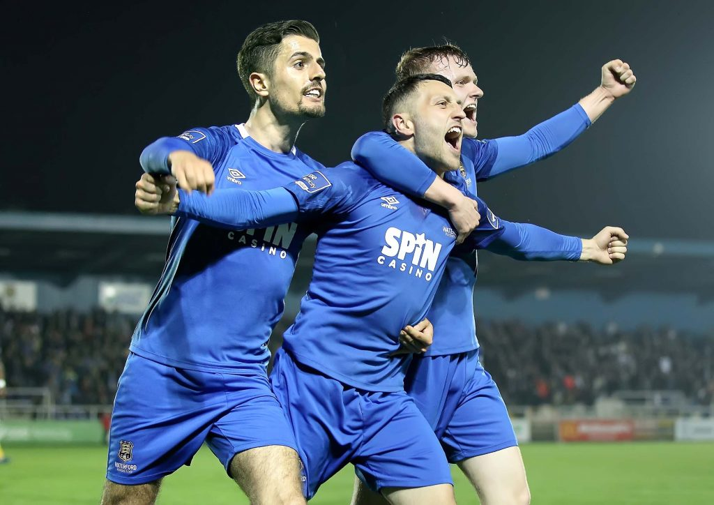 Waterford FC's Shane Duggan celebrates with team mates, Zack Elbouzedi and JJ Lunney after opening the scoring for his side. Photos: Noel Browne