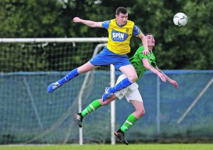 Waterford FC's Dean Walsh climbs high and hard to win this aerial duel with Irish Universities Dean Kelly.