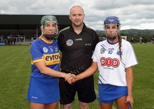 Referee Andrew Larkin pictured with Waterford captain, Niamh Rockett and Tipperary captain, Clodagh Quirke.