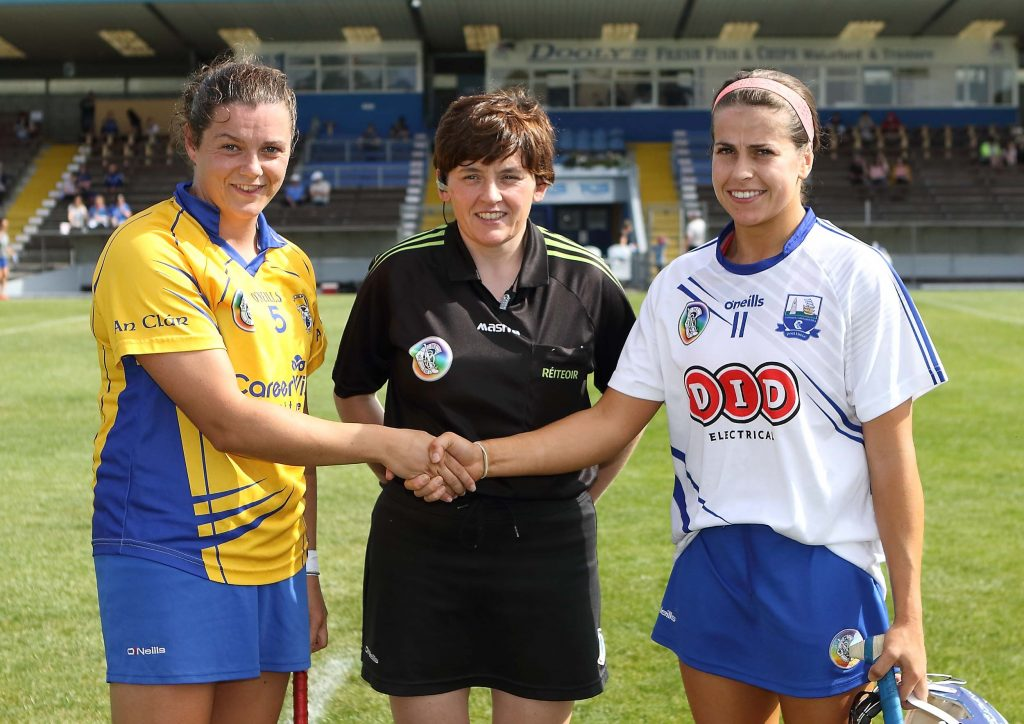 Referee Liz Dempsey pictured with Waterford captain, Niamh Rockett and Clare captain, Laura McMahon.