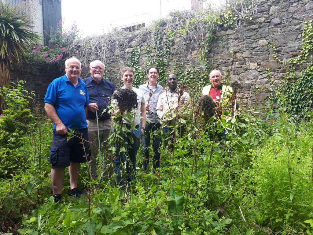 Group pictured amongst the overgrown vegetation before work began at the site.