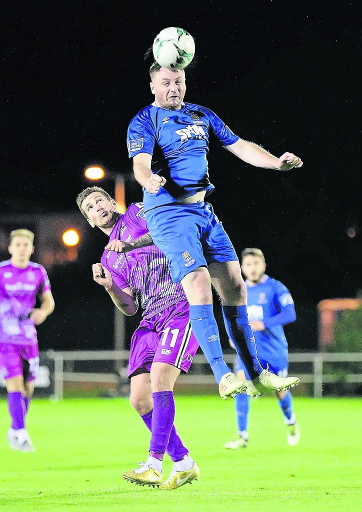 Waterford FC's Kenny Browne heads clear ahead of Dundalk's Patrick McEleney.